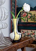 White ranunculus in small 60s vase; traditional cabinet in peasant painting style in background