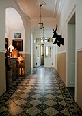 Pale hallway in manor house with traditional, black and white marble floor and hunting trophies on wall