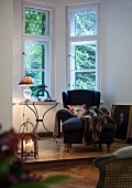 Comfortable reading corner with wing back chair and candle lantern on platform in window bay