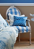 Antique chair covered in blue and white checked fabric with polka dot scatter cushion against beige wall