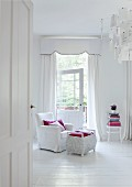 Bedroom entirely in white - armchair with white loose cover and white-painted wicker trunk on white wooden floor in front of white, floor-length curtains