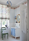 Romantic bathroom with floral wallpaper frieze in nostalgic country-house style and oval, gilt-framed mirror