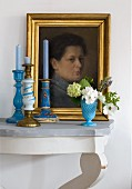 Blue candles in candlesticks and vase of flowers in front of oil painting on wall bracket