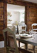 Antique French chairs with grey-painted wooden frames at hand-crafted, Italian dining table in front of open doorway leading to kitchen