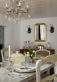 Festively set table in rustic dining room with chandelier hanging from white wooden ceiling