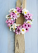 Wreath of pink and white daisies on wooden board