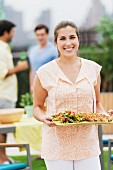 Woman holding tray of barbecued food & salad
