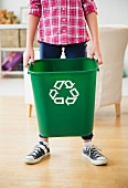 Boy carrying bin with recycling symbol