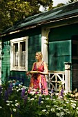 Blonde woman outside wooden house in Sweden
