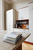 Open cookery book on counter with marble worksurface in front of fitted cupboards with white doors and wooden worksurface