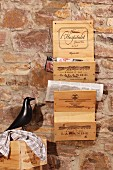 Newspaper rack hand-crafted from old wine crates hanging on rustic stone wall next to black bird figurine