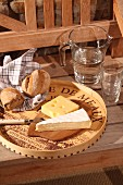Cheese board upcycled from old wine crate with chip wood edge; carafe of water and glasses on wooden bench