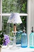 Hand-crafted lampshade in blue and white toile de jouy fabric and vintage soda siphons on windowsill