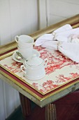 White coffee set on tray covered with red-and-white Toile de Jouy fabric