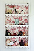 Plate rack with back lined in red and white toile de jouy wallpaper
