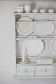 Serving platters and crockery on white-painted plate rack