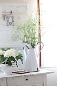 Wiesenblumen in einer Emaillekanne und Hortensien in der Suppenterrine