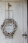 White-painted willow wreath on shabby-chic front door