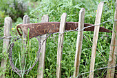 Rusty scythe blade used as sign on paling fence