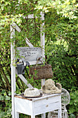 Old lowboy decorated with bric-a-brac in garden