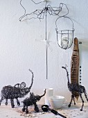 Black, wire sculptures of African animals and other wire objects against white wall