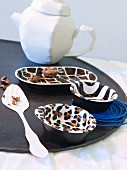 Various bowls painted with different animal-skin patterns arranged on black tray