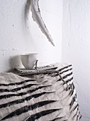 White cup on top of grey and black scatter cushion