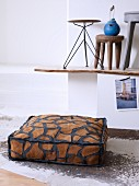 Floor cushion with animal-skin pattern on animal-skin rug and various stools on rustic, wooden surface