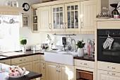 Cremefarbene Einbauküche im Landhausstil mit Kassettentüren und grossem Aufsatzspülbecken aus Keramik