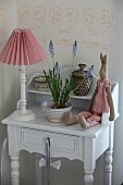 Table lamp with red and white lampshade, plush rabbit and grape hyacinths on small, shabby-chic cabinet