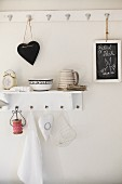 Heart-shaped board hanging from wall hook and shelf holding classic alarm clock, ceramics and reel of red and white ribbon; sketch of rabbit on chalk board