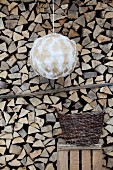 Pendant lamp with hand-crafted spherical lampshade in front of stacked firewood