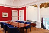 Landing with red-painted walls in grand villa - table and blue-covered armchairs at head of stairs with Corinthian columns below stucco picture rail
