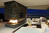 White sofa combination and open fireplace in stone-tiled partition; panoramic view of city by night in background