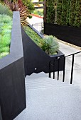 View down flight of pale concrete steps between black metal balustrade and black wall of terraced garden