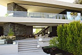 Terrace with outdoor furniture and decorative white balls on steps below upper storey of contemporary house with glass balcony balustrade