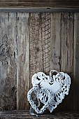 Two old fashion christmas hearts on a wooden wall