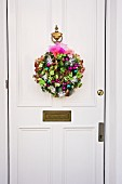 Pink and green dried Hydrangea flower, Christmas wreath on white front door