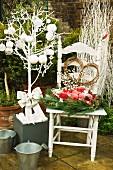 Weisslackiertes Bäumchen mit Kugel- und Sterndeko neben weihnachtlichem Gesteck auf Holzstuhl