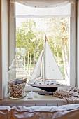 Maritime arrangement of sailing boat model and glass jar of shells on windowsill