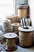 Collection of twine, some on old wooden reels, in corner of windowsill