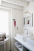 White, shabby-chic bathroom with large countertop sinks on washstand with towel compartments