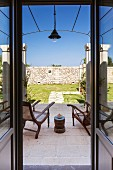 View through open terrace door of antique chairs on stone floor in front of sunny, Mediterranean garden