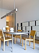Wooden chairs around table with curved top below designer pendant strip light; contemporary shelving with white, sliding fronts against wall