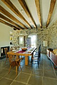 Set dining table with light and dark wooden chairs in Mediterranean dining room with stone walls and wood-beamed ceiling