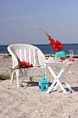Vase of gladioli, maritime ornaments and glass of champagne on folding table next to wicker chair on sandy beach