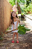 Little girl in garden holding large rhubarb leaf