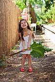 Little girl in garden holding large rhubarb leaf