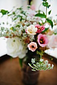 Bouquet of spring wedding flowers on top of a wine barrel in a rustic setting