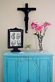 Pink roses and framed anatomical drawing on blue wall cabinet below crucifix